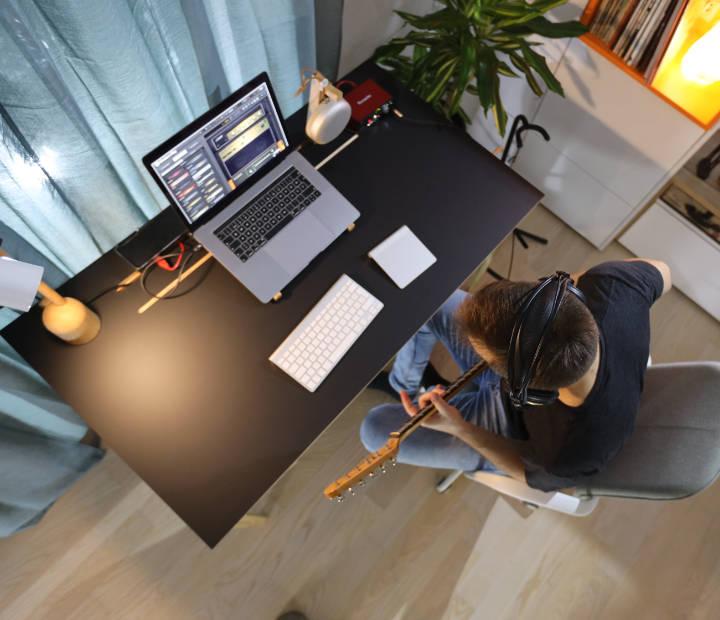 Pogled odozgo na površinu crnog radnog stola Conform Deska i gitarista koji snima glazbu uz svoj setup