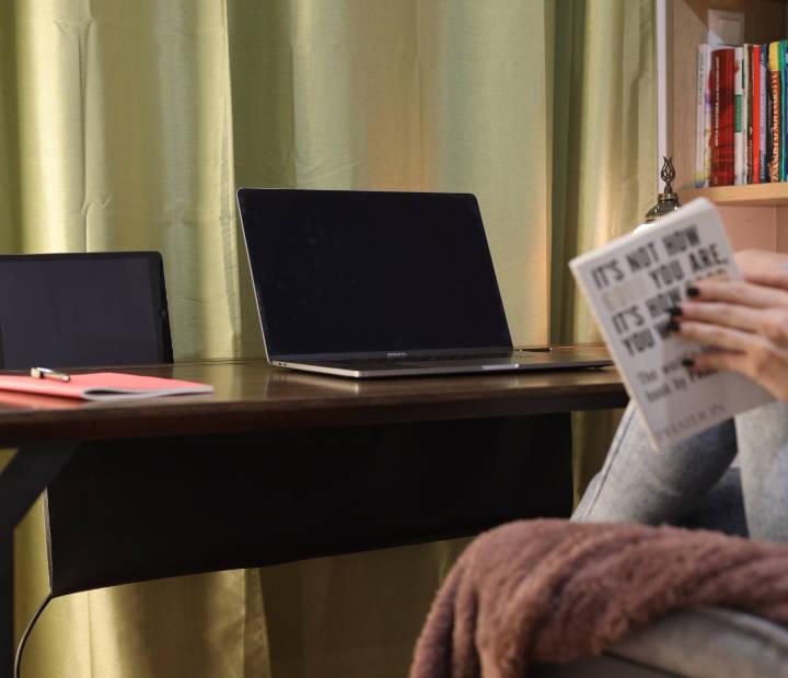 Djevojka čita, a ispred nje je smeđi radni stol Conform Desk na kojemu se nalazi računalo, ipad i bilježnica
