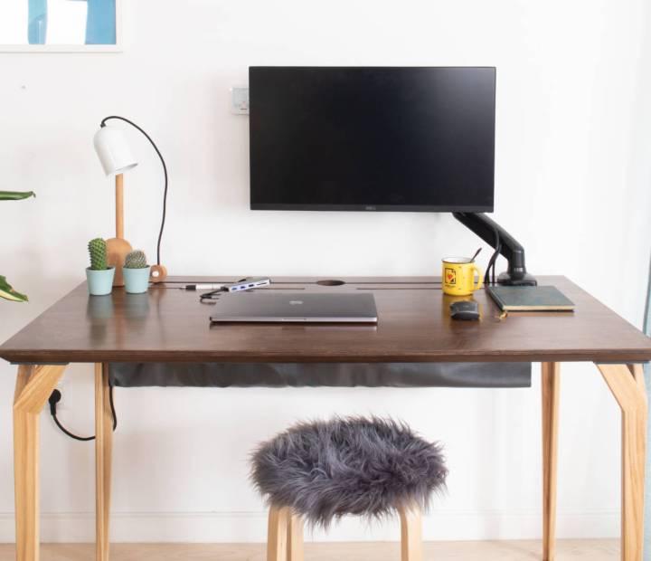 Prikaz smeđeg radnog stola Conform Desk u prostoru s nosačem monitora, laptopom, lampicom, bilježnicom i šalicom