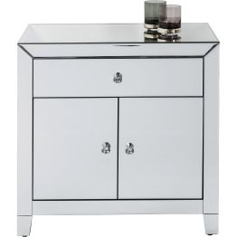 Spiegelnde Oberflächen und facettierte Griffe machen die Kommode zum wahren Eyecatcher in jedem Raum. Mit einer Schublade und zwei Türen dient sie zum Beispiel als Cocktailschränkchen. Die Serie enthält weitere Modelle.