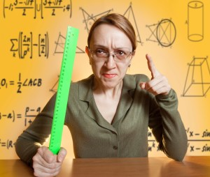 Stern looking teacher is pointing and weilding a brightly colored ruler