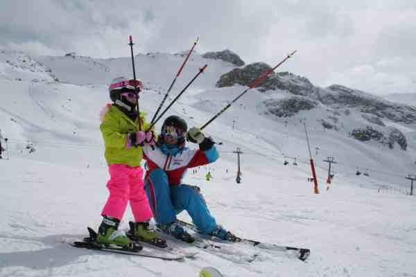 Kind und Skilehrer im Skikurs