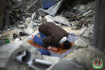 A Palestinian man prays in the rubble of his house in Beit Lahiya, in the northern Gaza Strip