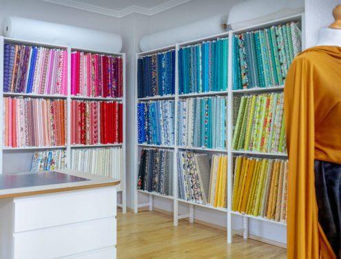 Große Farbpalette an verschiedenen Patchworkstoffen farblich sortiert im Regal.