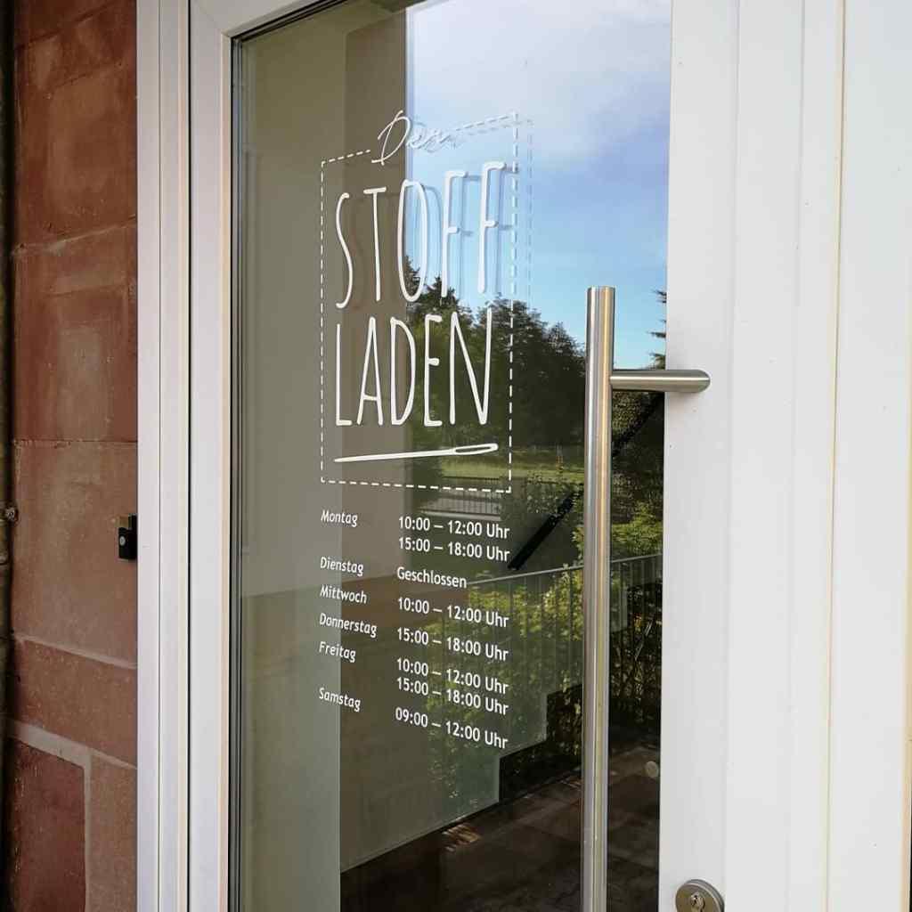 Unsere Eingangstür mit der Beschriftung in weiß auf Glas. Man sieht das Logo und die Öffnungszeiten des mollipolli Stoffladens