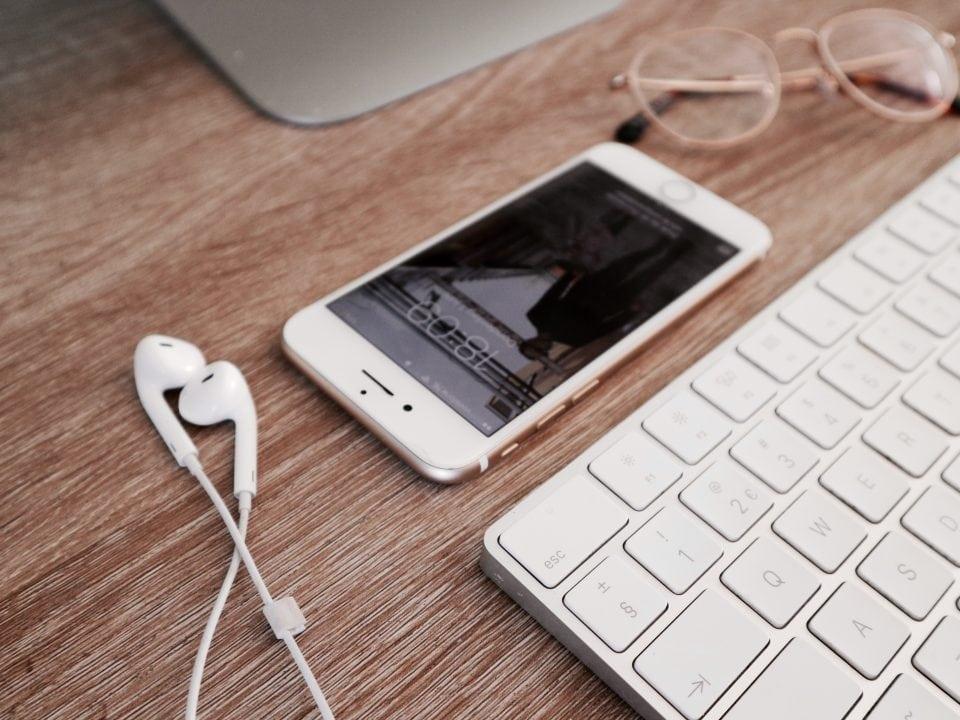 voordelen thuiswerken iPhone oordopjes werkplek georganiseerd YouTube op de achtergrond