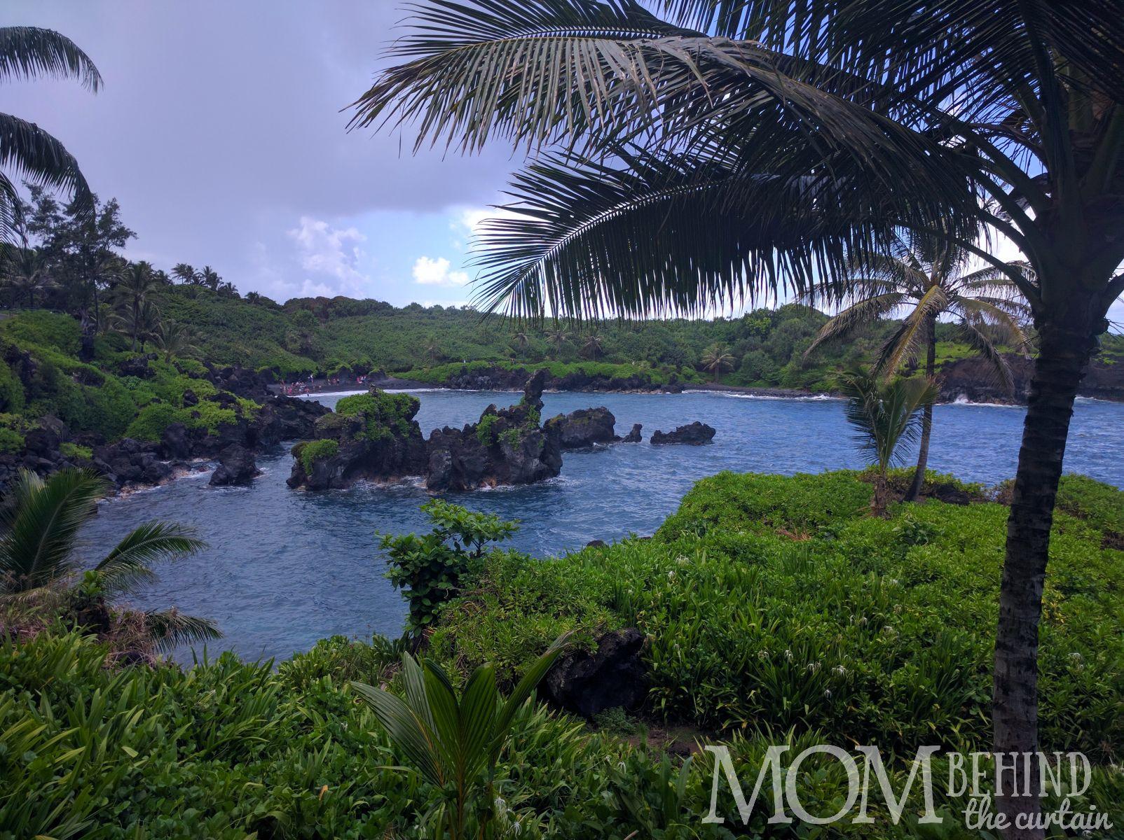 view of swimmers on black sand beach on the Road to Hana, Maui, Hawaii