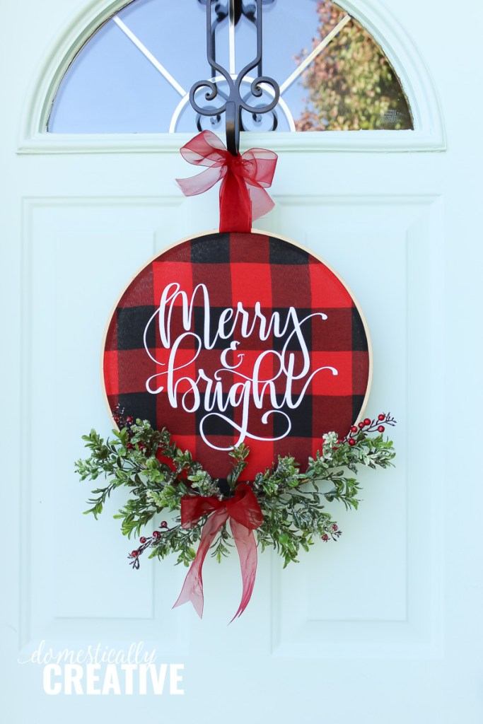 12+ of my favorite Christmas wreath tutorials, including this Checked Hoop Wreath! Learn how to make wreaths to decorate your home, everywhere from your front door to your kitchen! The wreaths use everything from fresh evergreens to these puzzle pieces (a genius way to save money when you make your wreath. You gotta see it!) and everything in between. Check it out to get some fabulous ideas.
