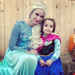 Mom and Daughter dressed as Anna and Elsa from Frozen smiling together. Examples of non-candy Halloween treats and activities