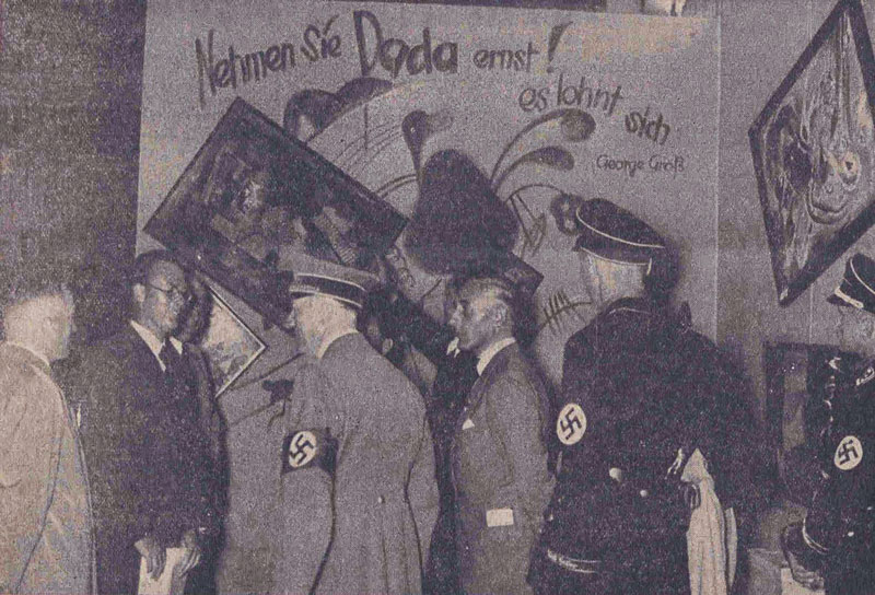 "Adolf Hitler and other Nazi officials take in the Dada wall at the ""Entartete Kunst"" (""Degenerate Art"") exhibition in Munich on July 16, 1937. Originally published in the Nationalist Observer, South German issue, No. 199, July 18, 1937."
