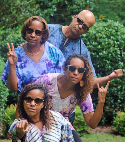 Family of 4 in colorful shirts in totem pole formation