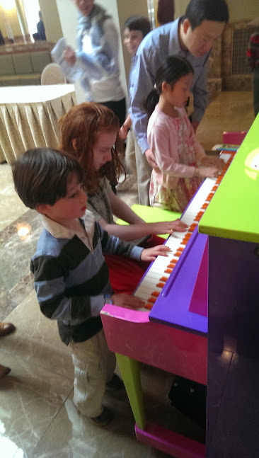 """Enjoying part of the """"musical petting zoo"""" they had set up in the lobby for all the young patrons."""