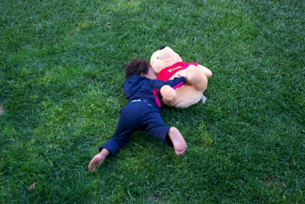 Girl rolling in grass with stuffed animal, Pooh