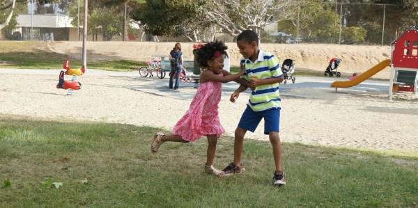Kids playing tag at the park, summer fun