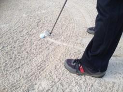 Disturbing sand in bunker. golf rules