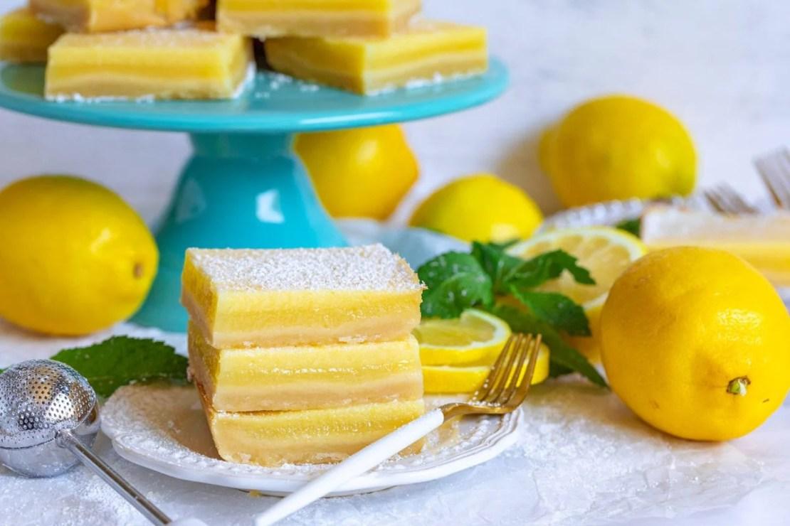 lemon bars on plate and cake stand with fresh lemons and mint.