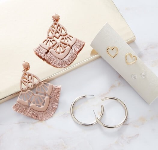 Photo of EAR PARTY $59 ($146 value) set including four pairs of earrings on a gold color tray with white marble background.