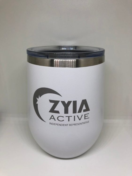 Photo of a white and silver wine tumbler with lid and black Zyia Active logo printed on it. Tumbler is sitting on a white surface with a white background.