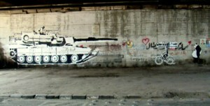 Ganzeer's tank versus bike (with Sad Panda in melancholy pursuit), under the October 6th Bridge. Copyright suzeeinthecity.wordpress.com.