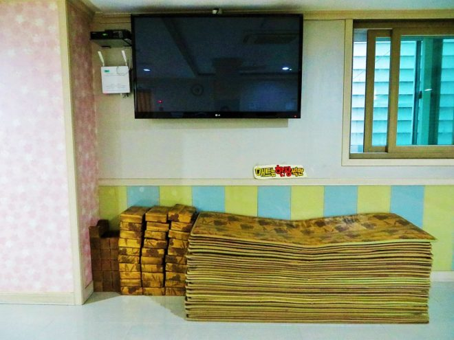 Tv, mats and pillows in the common area of a jjimjilbang in South Korea