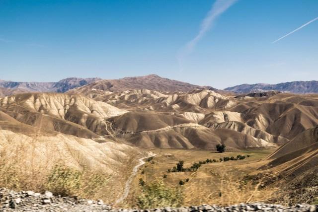 estrada de terra indo pelas montanhas do Quirguistão