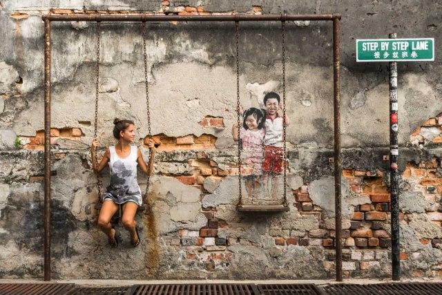 Fernanda em um balanço na arte de rua de Penang