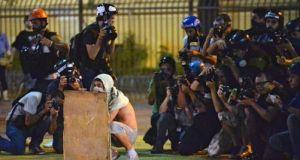 Un manifestant se protège de la police. Derrière lui, de nombreux photographes couvrent la manifestation anti-Mondial de football, le 22 février à Sao Paulo. | AFP/NELSON ALMEIDA