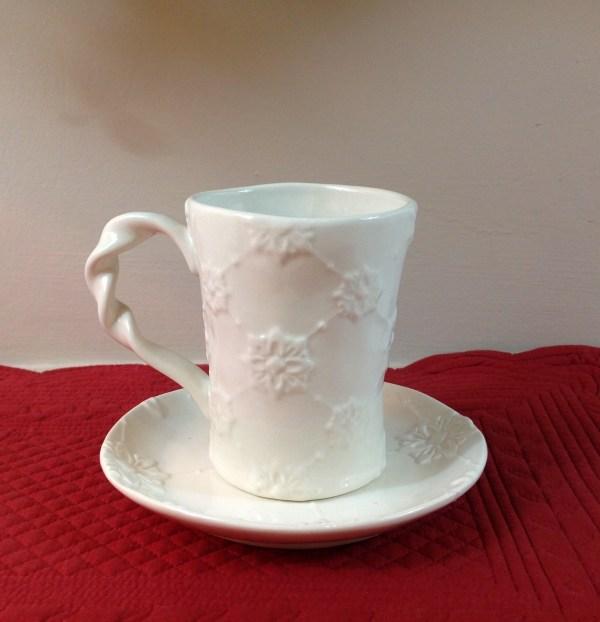 tazza con piattino in ceramica lavorata