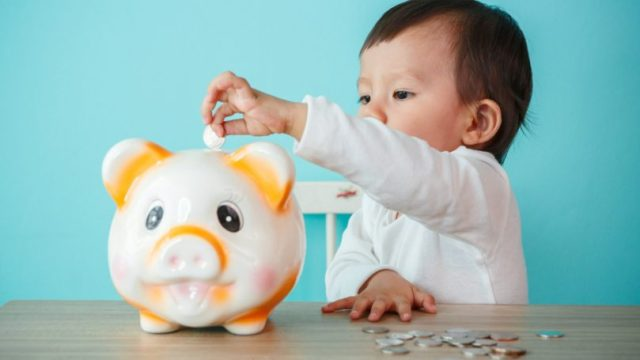 Baby Putting Coin In Piggy Bank Savings Allowance