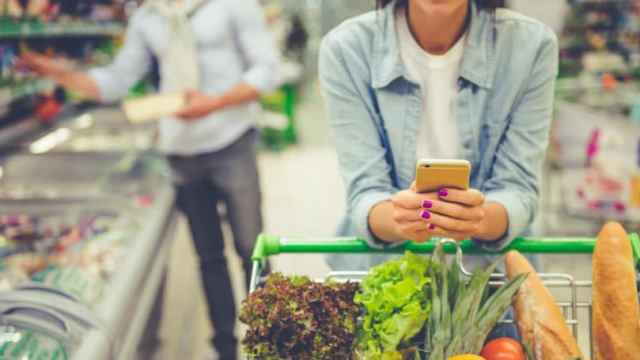 Shopping At Supermarket Cart Looking At Grocery List On Phone