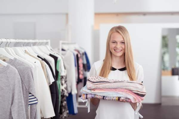 Young female personal shopper holding pile of clothes