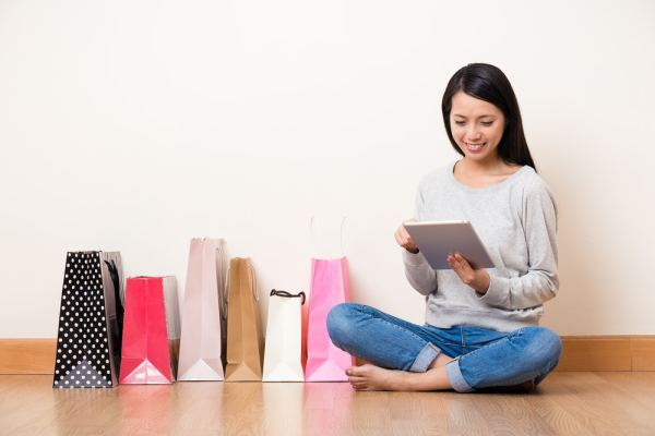Woman with shopping bags using a tablet