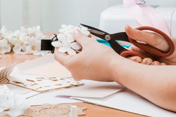 Someone cutting lace flowers for scrap-booking