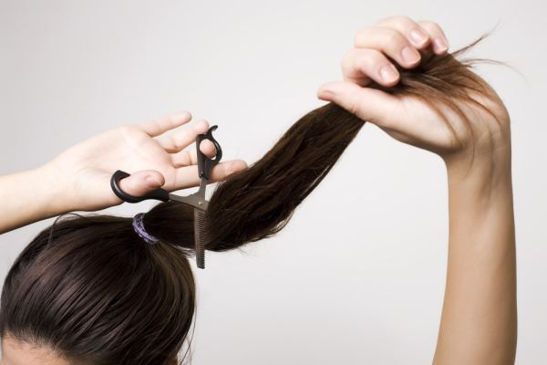 Woman cutting her ponytail off