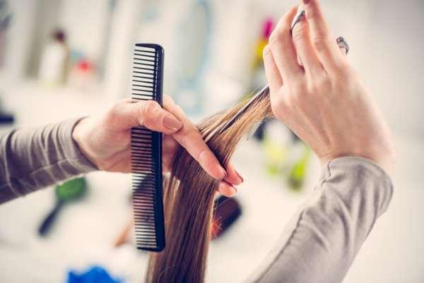 Hairdresser trimming long hair