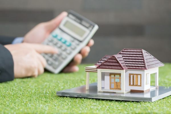 Someone using calculator in background and house model in foreground