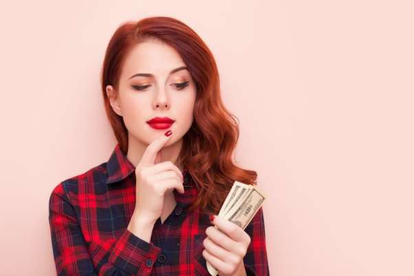 Woman looking at money in her hand quizzically