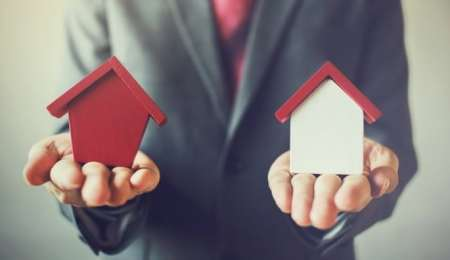 Business man holding two house models in different colours