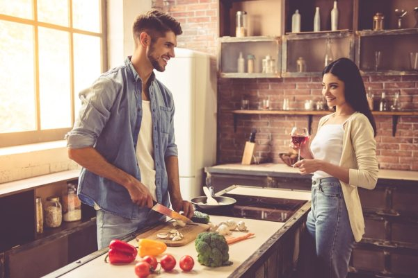 Man preparing dinner while woman watches on smiling