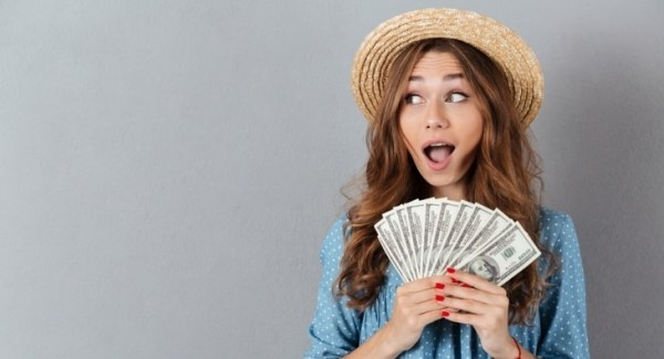 Shocked woman holding money
