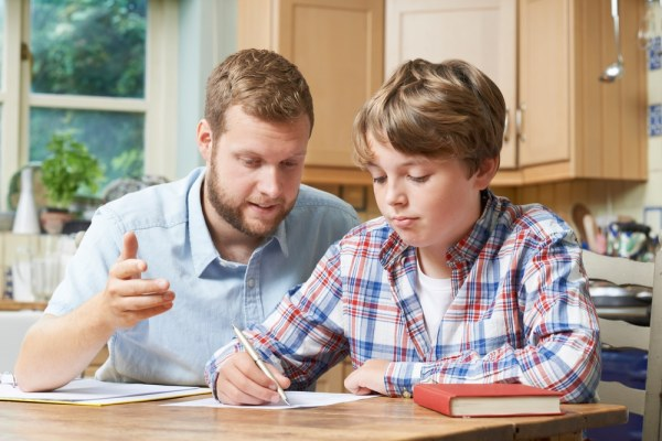 Young male tutor teaching young boy