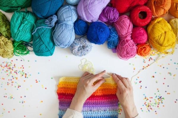 Woman knitting rainbow scarf