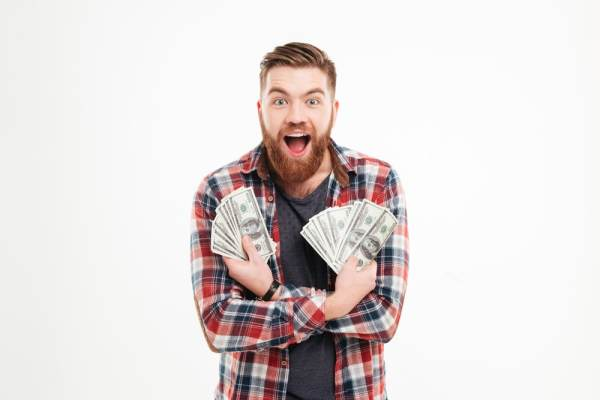 Excited male student holding handfuls of cash