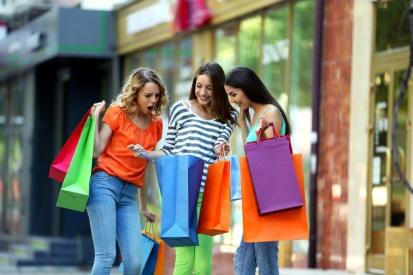 Three women stood on the high street looking in shopping bags excitedly