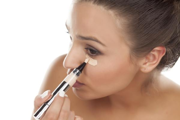 Woman applying concealer under her eye