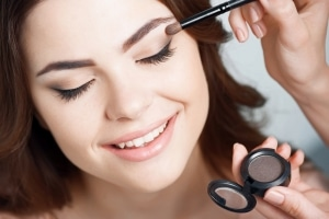 Woman having eyeshadow applied to her eyelid with a brush