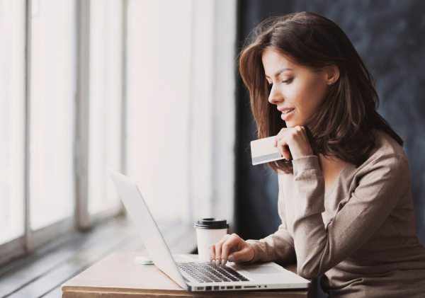 Young woman holding a credit card and using a laptop to shop online
