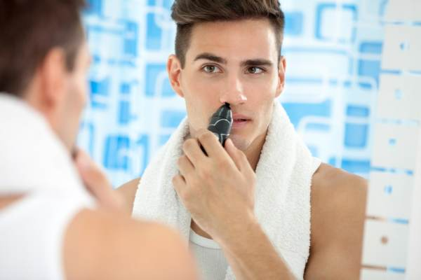 Young man using a nose hair trimmer