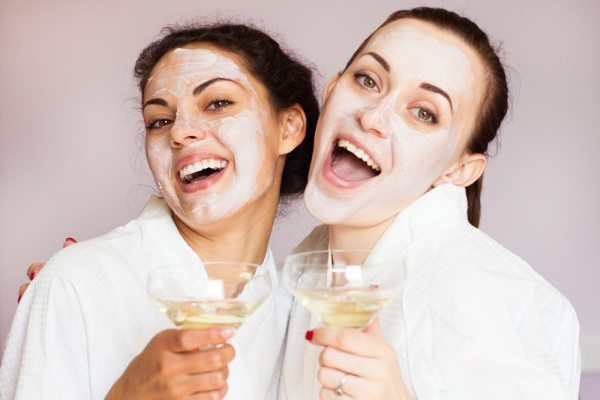 Friends wearing face masks and drinking champagne