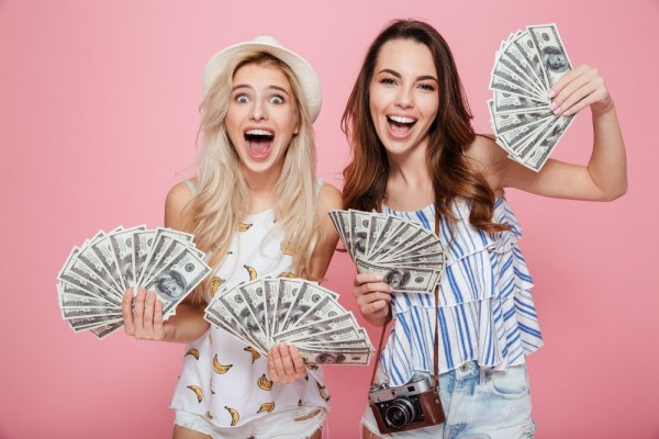 Excited girls holding big hand fulls of money